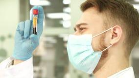 Doświadczony laborancki asystent ostrożnie egzamininuje próbnej tubki z krwią obrazy stock