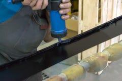 Doświadczony mężczyzna w pracujących ubraniach stosuje czarnego sealant zdjęcia stock