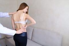 Doświadczony męski ortopeda diagnozuje młodej kobiety która narzeka Obrazy Stock