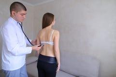 Doświadczony męski terapeuta diagnozuje młodej kobiety która przychodził rec Obrazy Royalty Free