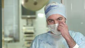 Doświadczony młody chirurg, poważny mężczyzna jest ubranym twarzy maskę patrzeje w kamerę zbiory