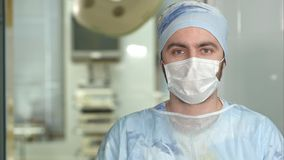 Doświadczony młody chirurg, poważny mężczyzna jest ubranym twarzy maskę patrzeje w kamerę Obrazy Stock