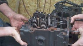 Doświadczony mechanik czyści samochodowego szczegół i naprawia zbiory
