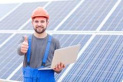 Doświadczony pracownik słonecznej baterii stacja trzyma laptopand przedstawienia aprobata gest Zdjęcie Stock