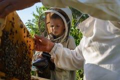 Doświadczony pszczelarka dziad uczy jego wnuk czułość dla pszczół Apiculture Pojęcie przeniesienie Zdjęcie Royalty Free