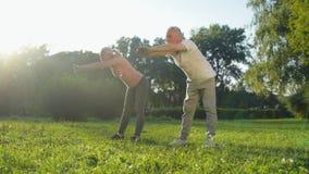Cheerful aged coupe enjoying warm up exercises outdoors