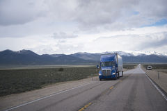 Do azul caminhão semi na estrada reta no platô de Nevada Fotografia de Stock