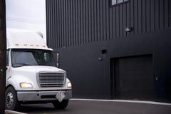 Do branco caminhão semi que está perto das facilidades de armazém Foto de Stock Royalty Free