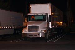 Do branco reflexão da luz do reboque do caminhão semi no parque de estacionamento dentro nigh Fotos de Stock