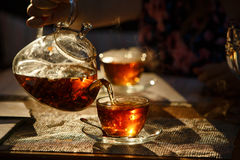 Do bule de vidro transparente derrame o chá preto na caneca de vidro, incandesce foto de stock royalty free