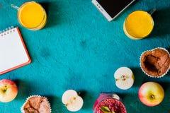 Do café da manhã vida ainda com caderno e móbil no fundo ciano imagem de stock