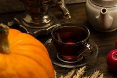 Do chá vida ainda com samovar, maçãs, abóboras alaranjadas maduras, folhas de bordo, trigo no fundo de madeira Imagem de Stock