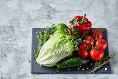 Do close-up vida ainda de legumes frescos sortidos e de ervas no fundo textured branco, vista superior, foco seletivo Fotos de Stock Royalty Free