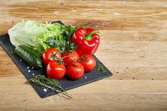 Do close up vida orgânica ainda de legumes frescos sortidos e de ervas no fundo de madeira rústico, topview, foco seletivo Imagem de Stock