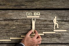 Do It concept of achievement and success. Illustrated with paper cutouts of men with one supporting the text as the other climbs up a flight of steps Royalty Free Stock Photo