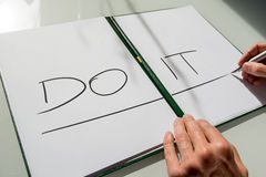 Do It concept. With the hand of a man writing the words in large capital letters across an open notebook conceptual of - do not procrastinate, do it immediately Stock Photography
