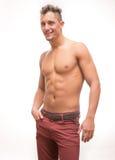 Do corpo descamisado das calças do homem novo sorriso modelo muscular Imagens de Stock