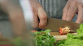 Do cozinheiro chefe pimenta doce vermelha dos cutts profissionalmente com a faca do ` s do cozinheiro chefe na placa de corte video estoque