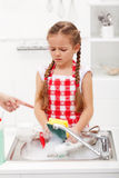 Do the dishes this instant - child ordered to wash up tableware. Do the dishes this instant - sad and grumpy little girl ordered to wash up tableware Stock Photo