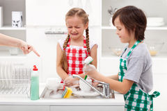 Do the dishes - kids ordered to help in the kitchen. Do the dishes - upset kids ordered to help in the kitchen by washing tableware Royalty Free Stock Image