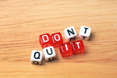Do It. Dont Quit  Do It written on red and white dices on wooden  background Royalty Free Stock Photography