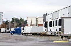 Do equipamento caminhão grande e semi reboques semi que estão na fileira na doca do armazém para carregar e descarregar a carga c imagem de stock royalty free