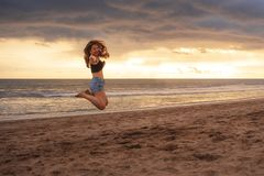 Do estilo de vida retrato fora da mulher coreana asiática feliz e bonita nova que salta entusiasmado louco na praia do por do sol foto de stock