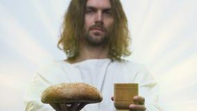 Do homem naco da terra arrendada de Jesus igualmente de pão e de vidro da videira nas mãos, comunhão filme