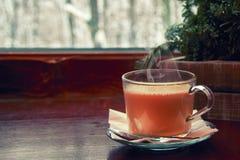 Do inverno vida acolhedor ainda: cacau quente do copo de vidro com vapor, na soleira de madeira contra a paisagem da neve da part Foto de Stock