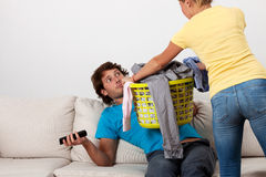 Do the laundry. A women giving her husband dirty clothes to do the laundry stock images