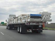 Do leito caminhão semi que transporta as tubulações fotografia de stock royalty free