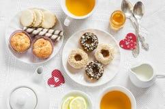 Do limão romântico do café da manhã do dia de Valentim chá verde e doces - queques da banana, cookies com caramelo e porcas, anéi Fotos de Stock