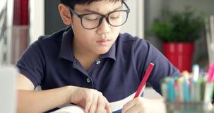 Do menino acautelar-se e fazer seus trabalhos de casa monóculo asiático em casa filme