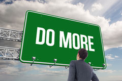 Do more sign against sky. The word do more and businessman standing with hand on hip against sky Stock Image
