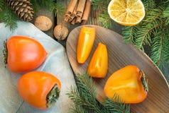 Do Natal vida ainda com caqui e canela na tabela de madeira Vista superior Imagem de Stock