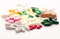 Do not be a medicine addict. Colorful and multi-shaped pills over wihte background Royalty Free Stock Image