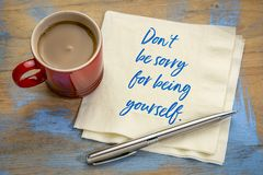 Do not be sorry for being yourself. Handwriting on a napkin with a cup of coffee royalty free stock image