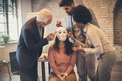 Do not be what you did not. Businesspeople paint a mask on a woman. Close up stock images