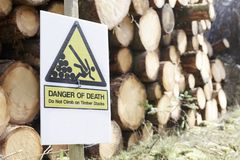Do not climb on chopped wood logs stacked danger of danger sign in forest woodlands stock photos