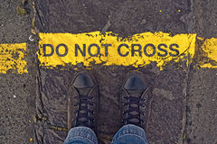 Do Not Cross The Line, On the Border. Male sneakers on the asphalt road with yellow line and title Do Not Cross. Border line concept, danger or warning sign Royalty Free Stock Photos