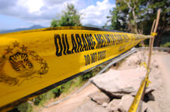 Do not cross - Police Line. A yellow police tape indicates the presence of a gorge, Indonesia Royalty Free Stock Photos