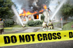 Do not cross tape with firefighters and a burning house. In the background Stock Images