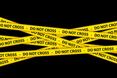 Do Not Cross Tape. Yellow caution tape strips with text of do not cross, on black background Royalty Free Stock Photography