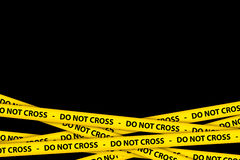 Do Not Cross Tape. Yellow caution tape strips with text of do not cross, on black background Royalty Free Stock Photos