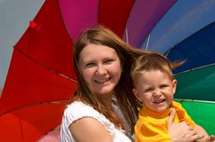 Do not depend on weather. Dont depend on weather conditions. Happy young woman and kid under brightly colored umbrella having fun outdoors Royalty Free Stock Photos