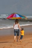 Do not depend on weather. Conditions. Happy young woman and kid under brightly colored umbrella walking along the beach Stock Photography