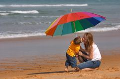 Do not depend on weather. Conditions. Happy young woman and kid under brightly colored umbrella having fun outdoors Royalty Free Stock Photo