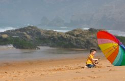 Do not depend on weather. Conditions. Cute small boy with big brightly colored umbrella having fun on the beach Royalty Free Stock Photo
