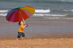 Do not depend on weather. Conditions. Cute small boy with big brightly colored umbrella having fun on the beach Stock Photo