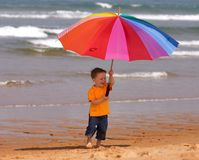 Do not depend on weather. Conditions. Cute small boy with big brightly colored umbrella having fun on the beach Royalty Free Stock Image